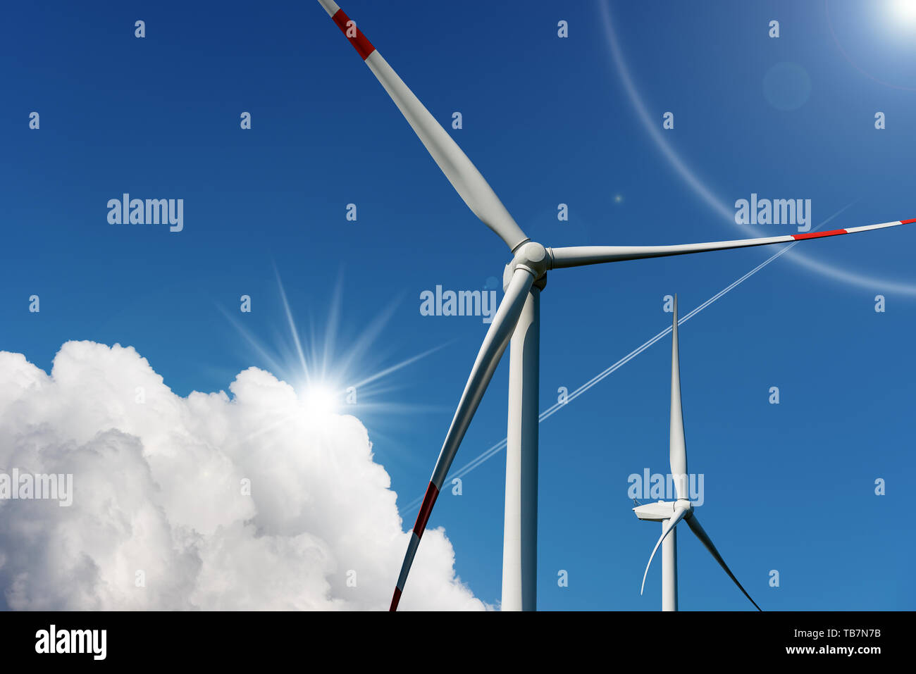 Two wind turbines on a blue sky with clouds and sun rays - Renewable energy concept Stock Photo