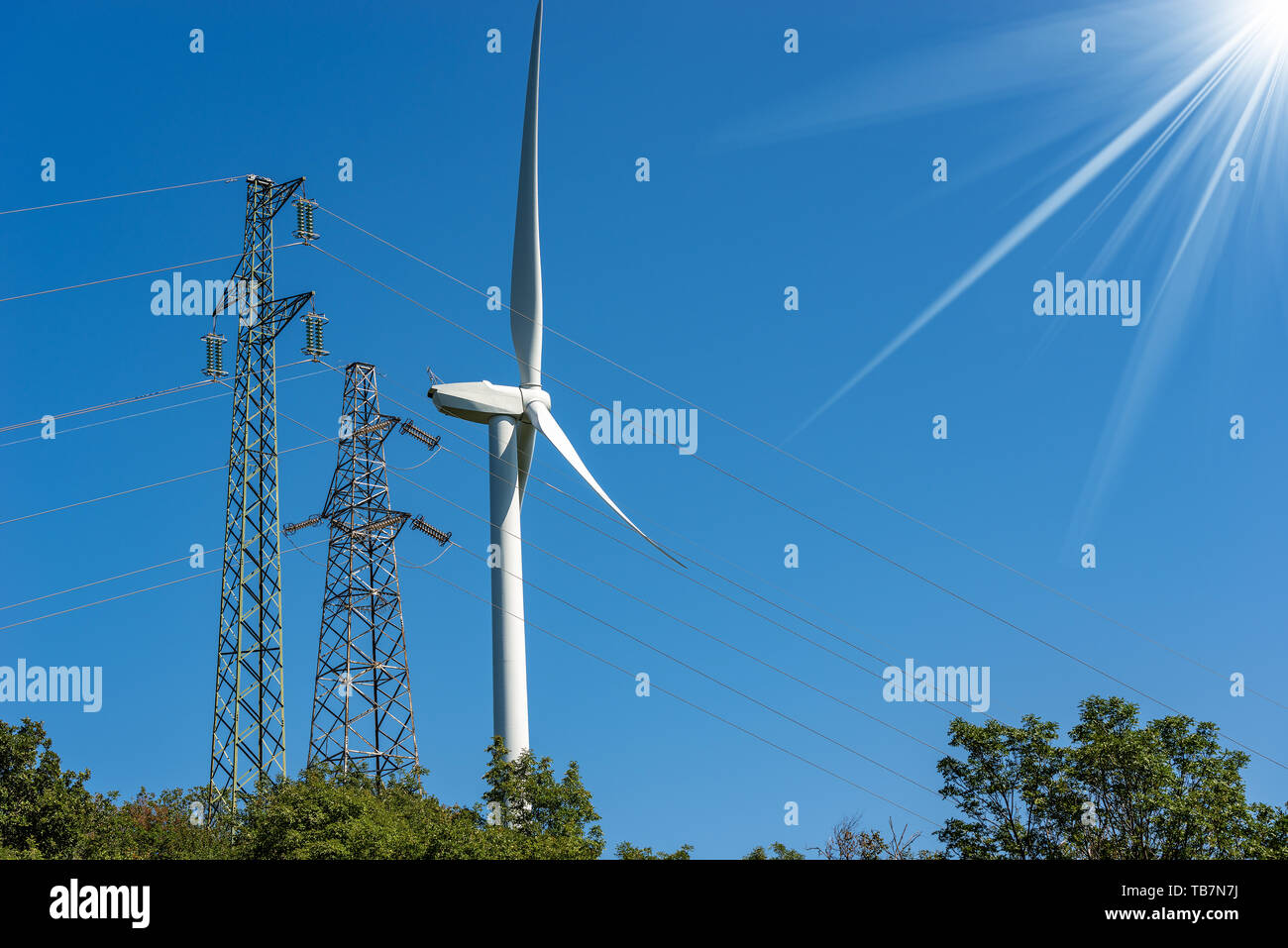 Wind turbine and high voltage towers (power line) on a clear blue sky with sun rays - Renewable energy concept Stock Photo