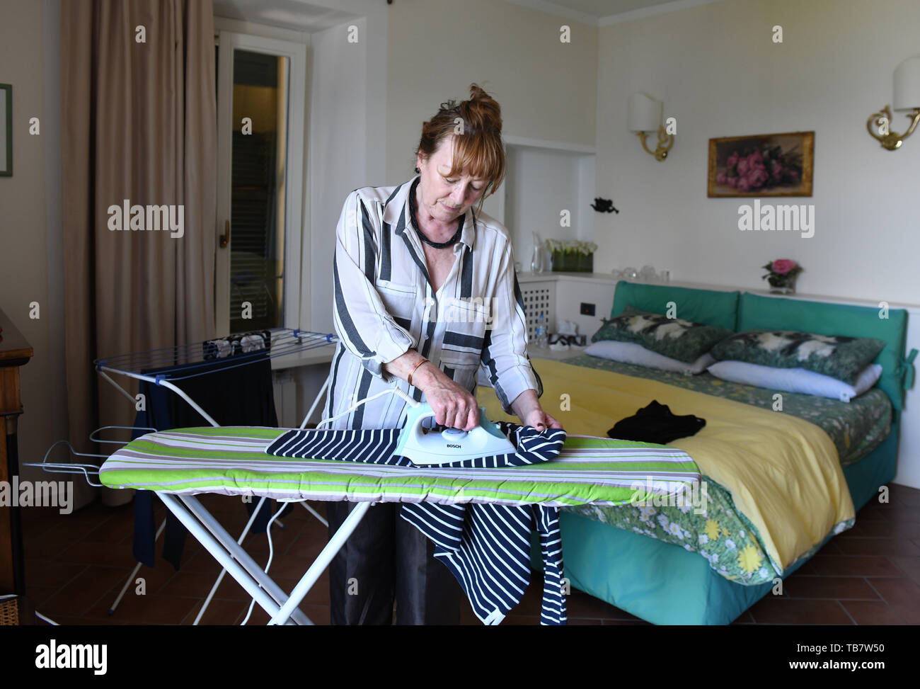 Woman ironing clothes on holiday - Stock Image