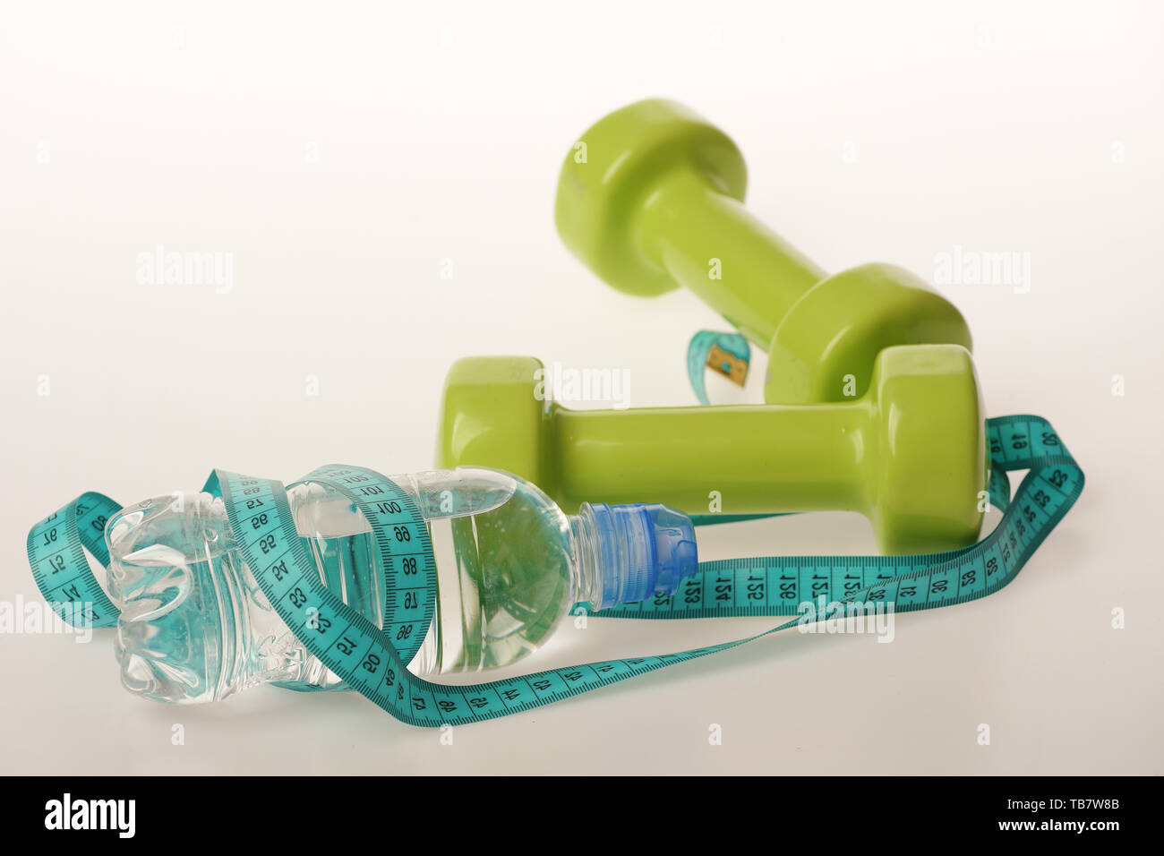 Water bottle tied with cyan blue measure tape by green dumbbells on white background. Athletics and weightloss concept. Refreshment and diet equipment. Bottle wrapped with tape by lightweight barbells - Stock Image