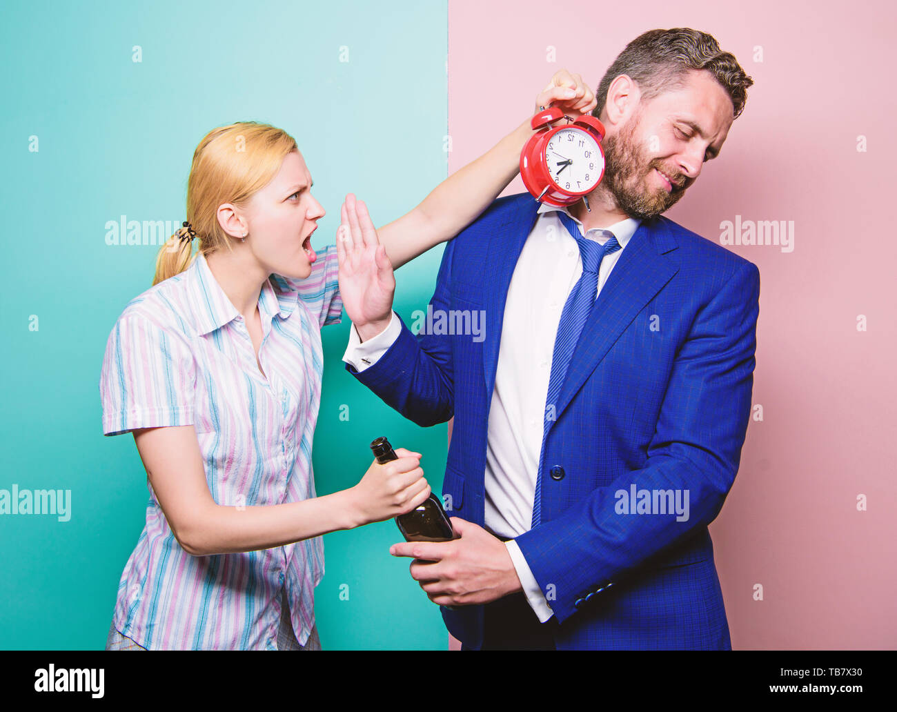What time is it. Businessman with alcohol bottle and woman with alarm clock. Man suffering from alcoholism. Angry wife meeting drunk husband late at home. Addictive alcoholism or alcohol abuse. - Stock Image