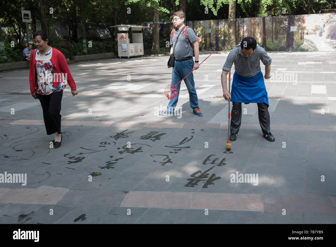 c10ab8be7 Elerly Chinese men practicing calligraphy on the ground at Huanhua Park,  Chengdu, Sichuan,
