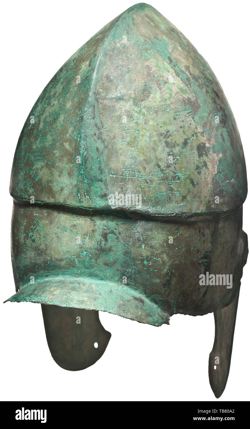 A Chalcidian helmet, type V, early 4th century BC, Bronze helmet with predominantly preserved, full-face tin plating. The brim decorated at the eye and ear cut-outs with a protruding contoured rib. A lancet-shaped nasal guard set between the eyes. Slightly arched neck guard offset from the skull by a small curve. The skull with a medial ridge dividing the top into two raised, hemispherical lobes. The carinated edge peaking into a contoured inverted 'V' above the recessed brow. The cheek pieces with two cut-outs connected to the ancient world, Additional-Rights-Clearance-Info-Not-Available - Stock Image