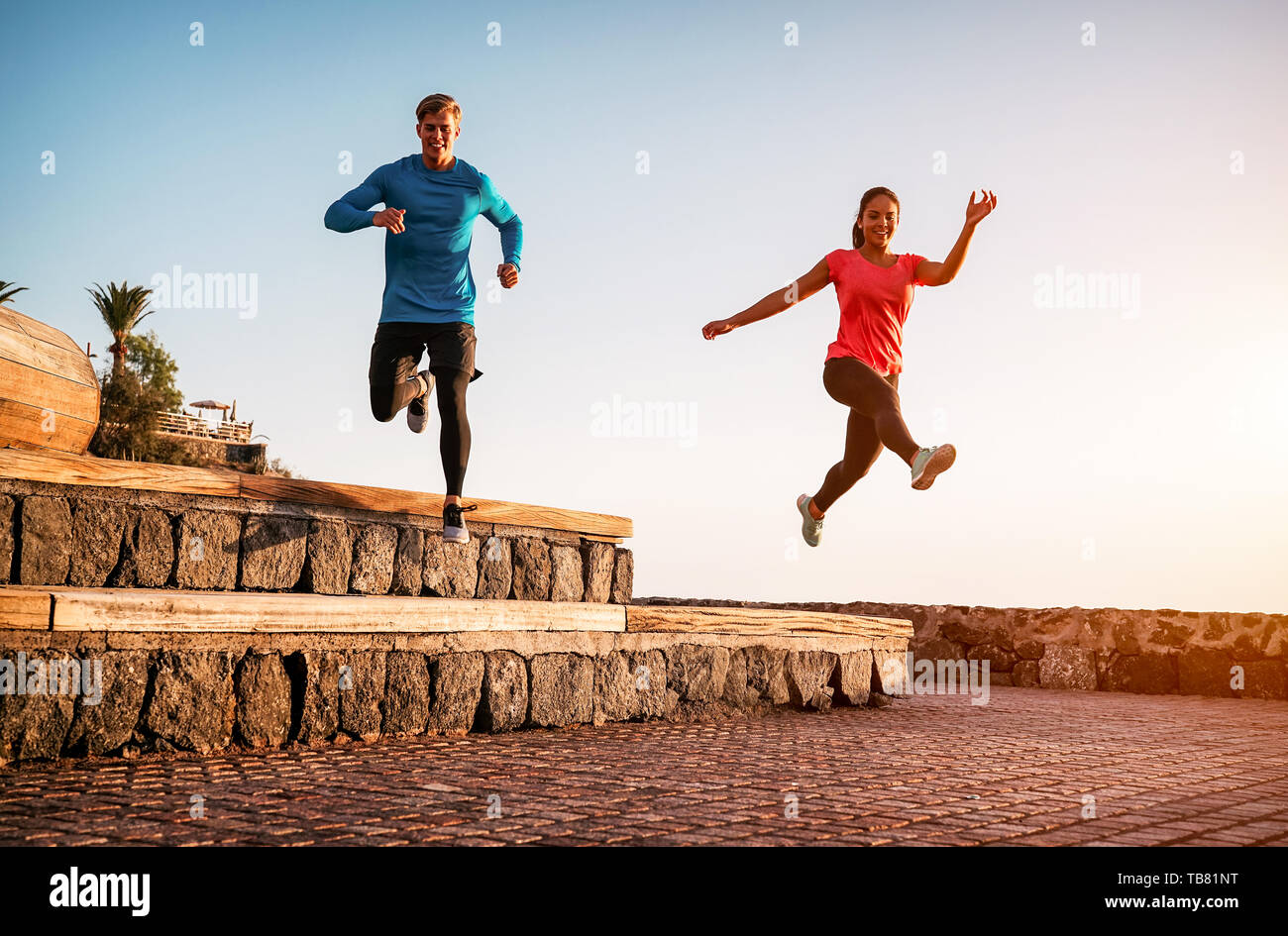 Fit couple doing workout running session at sunset outdoor - Sporty young people jogging next the beach - Healthy lifestyle and sport concept - Stock Image
