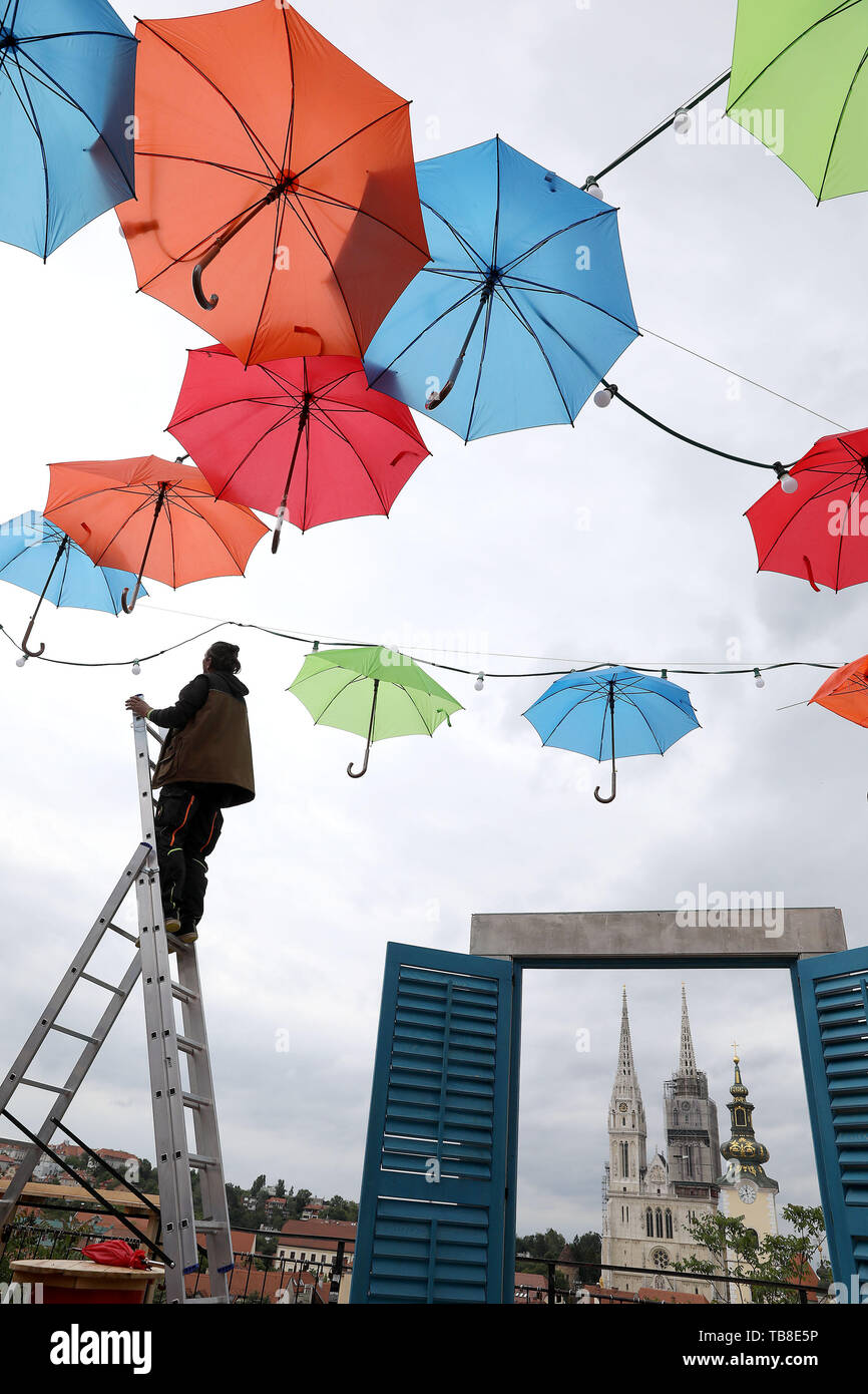 Zagreb, Croatia. 30th May, 2019. A worker hangs colourful umbrellas in preparation for Bas Nas Gourmet & Music Festival at the upper town of Zagreb, Croatia, May 30, 2019. Credit: Patrik Macek/Xinhua/Alamy Live News Stock Photo