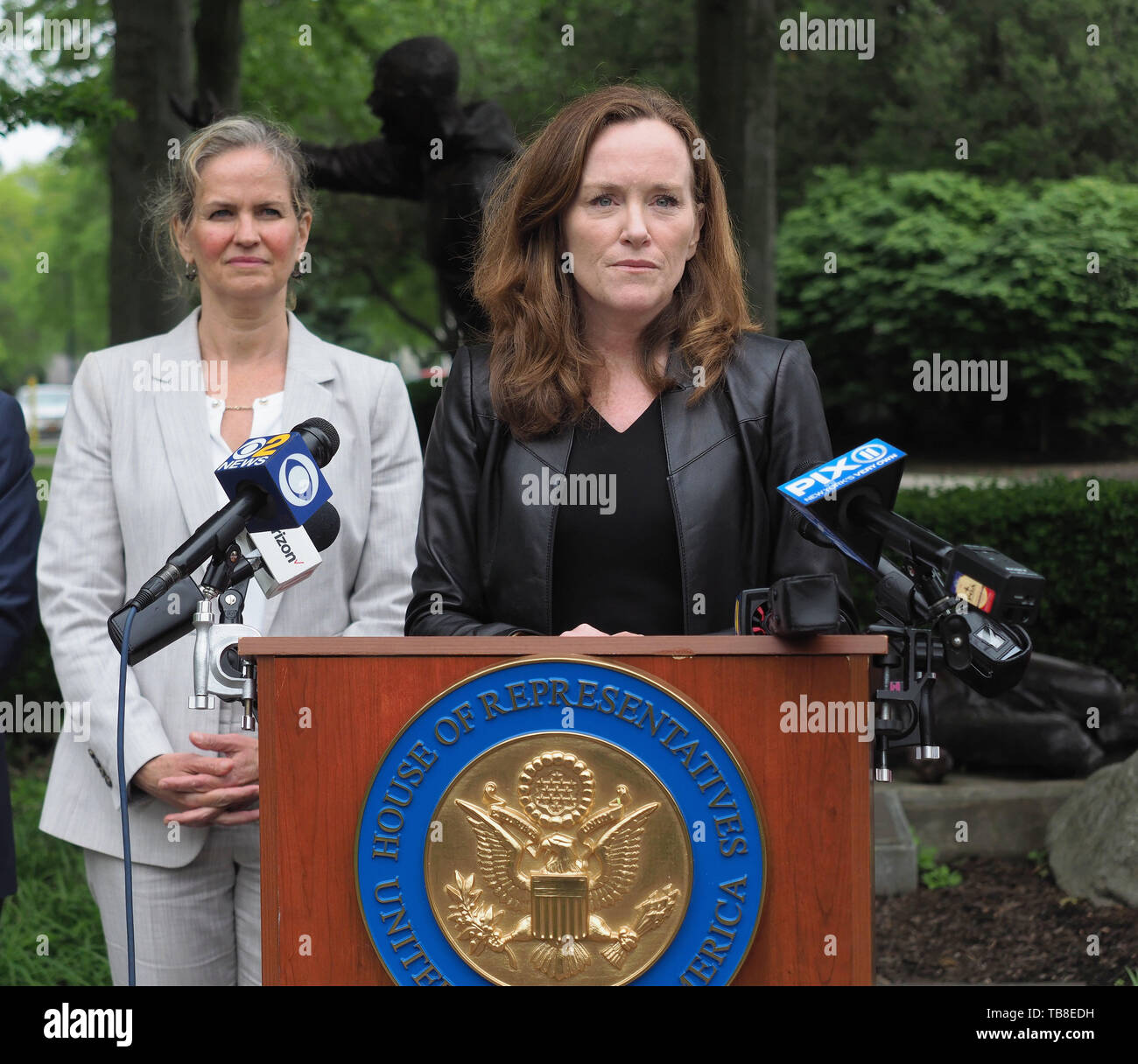 Hempstead, New York, USA. 30th May, 2019. At podium, U.S. Representative KATHLEEN RICE (NY-04) has a serious expression as she holds a press conference to announce she's introducing Three Bills to Congress to combat Impaired and distracted Driving, and at left is Nassau County Executive LAURA CURRAN, who thanked Rep. Rice for her safe driving legislation. Congresswoman Rice announced the package of 3 bills - End Drunk Driving Act, the Prevent Impaired Driving Child Endangerment Act, and the Distracted Driving Education Act of 2019 - at the Drunk Driving Victims Memorial in Eisenhower - Stock Image