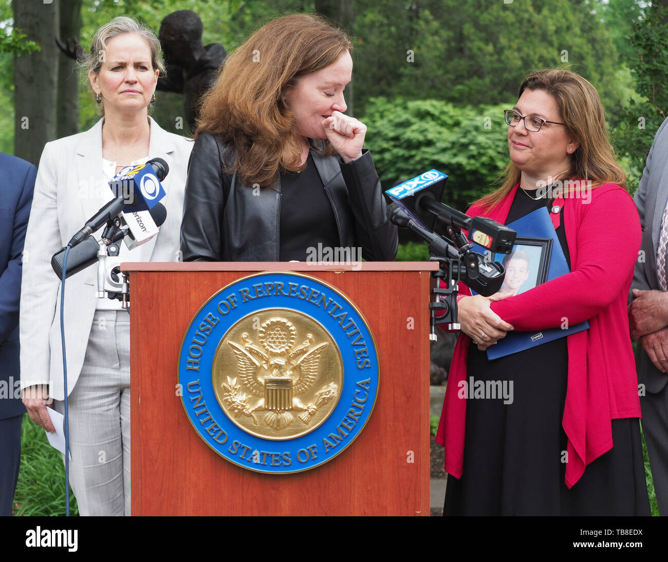 Hempstead, New York, USA. 30th May, 2019. At podium, U.S. Representative KATHLEEN RICE (NY-04) holds a press conference to announce she's introducing Three Bills to Congress to combat Impaired and distracted Driving. Her voice broke with sadness and she turned toward ALISA MCMORRIS, when the Rep. explained McMorris's 12-year-old son Andrew was killed by drunk driver exactly 8 months ago in Manorville while walking with a group of fellow Boy Scouts. At left is Nassau County Executive LAURA CURRAN. Congresswoman Rice announced the package of 3 bills - End Drunk Driving Act, the Prevent - Stock Image