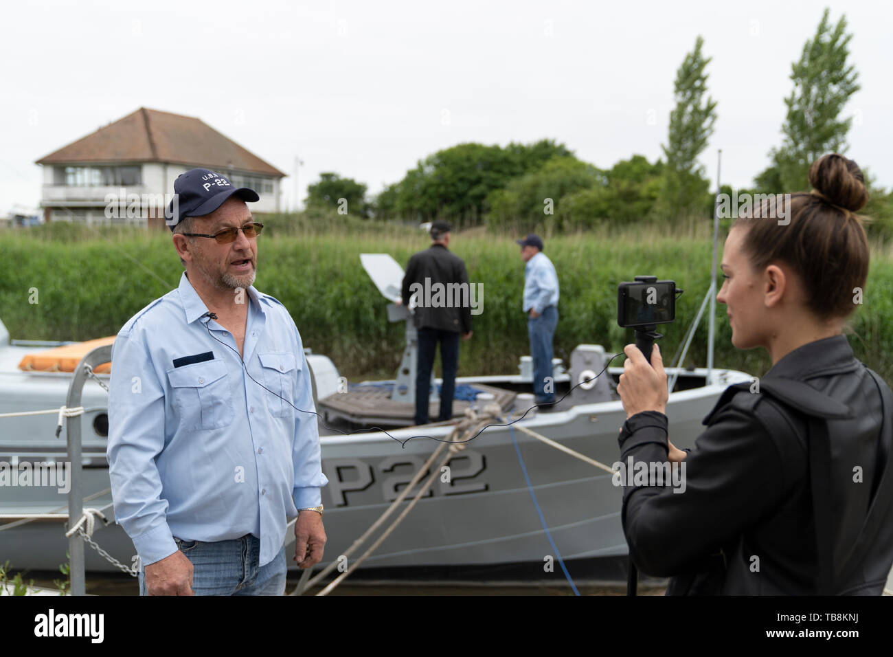 Mature Caucasian man being interviewed by young women with small video camera and microphone. Small motor launch on river quayside in background. Barry Field, captain and owner of P22, a restored Rhine Patrol Boat, being interviewed just before sailing to France for the 75th anniversary of the D-Day landings. Stock Photo