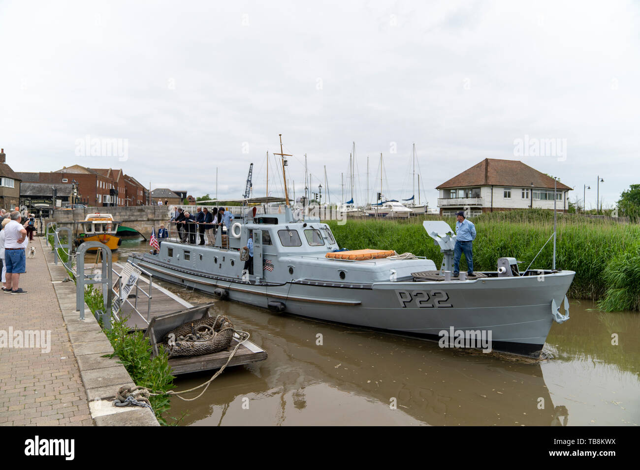 P22, a US built Rhine River Patrol boat from the 1950's, casting off from the quay side at Sandwich for France where it will take part in the 75th anniversary of D-Day. American patrol boat leaving morring in small river with people on the quay watching and waving. Stock Photo