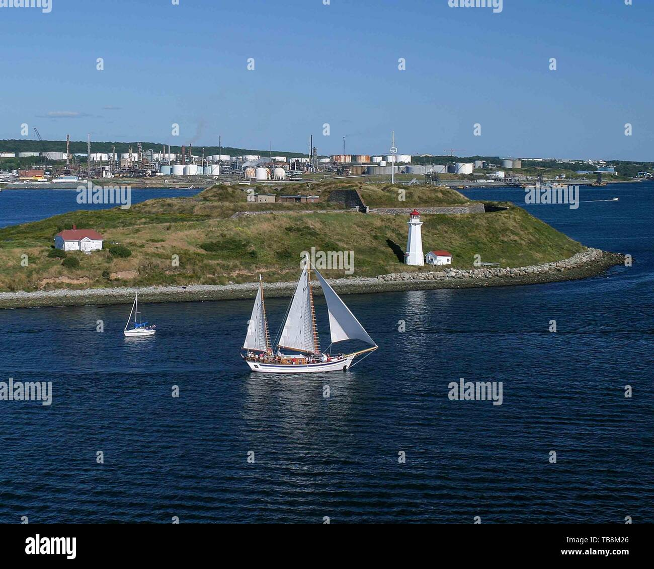 Halifax, Nova Scotia, Canada. 5th Sep, 2005. A schooner carrying visitors on a tour of Halifax harbor, Nova Scotia, passes St Georges Island and its lighthouse. Halifax and Nova Scotia are popular tourist destinations. Credit: Arnold Drapkin/ZUMA Wire/Alamy Live News - Stock Image