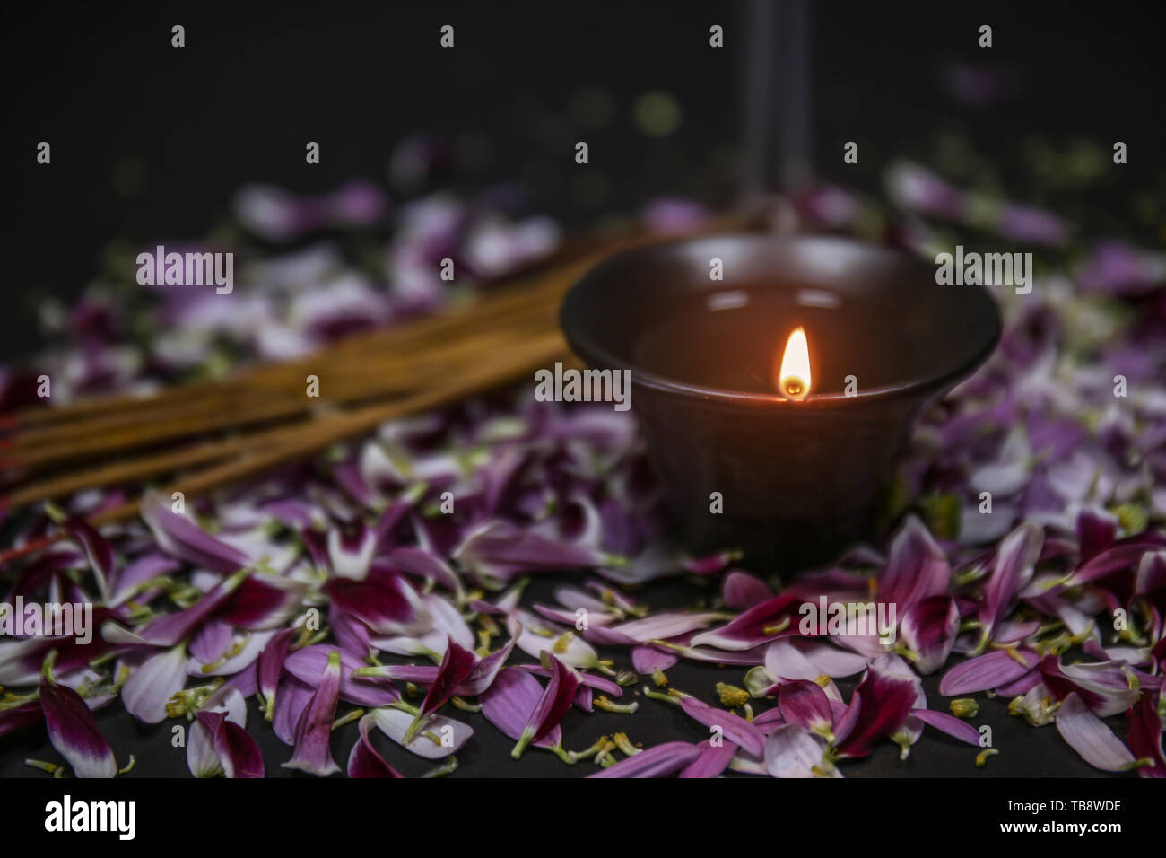 Burning candle with flower petals for celebration of Divaly