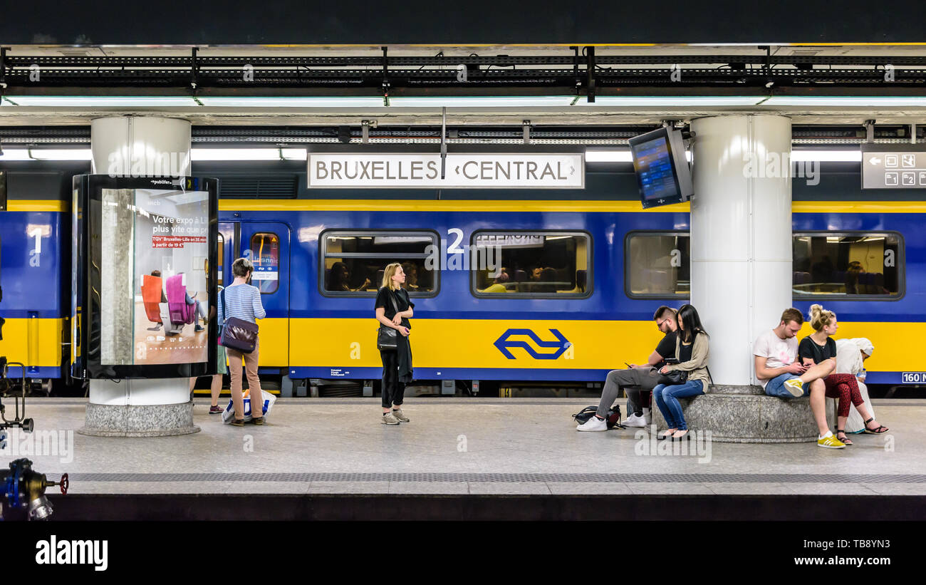 Brussels, Belgium - April 20, 2019: Passengers waiting on an underground platform in Brussels central station while a train from the dutch railway com - Stock Image