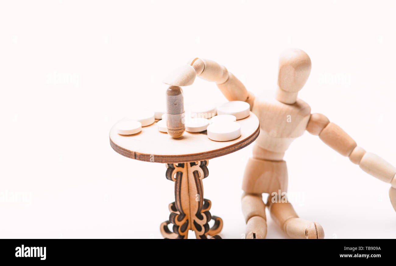Health care and medical treatment. Pills on tiny wooden table. Medication regimen. Human wooden dummy near table with medicines. Tips tackling complex medication regimen. Take medicines after food. - Stock Image