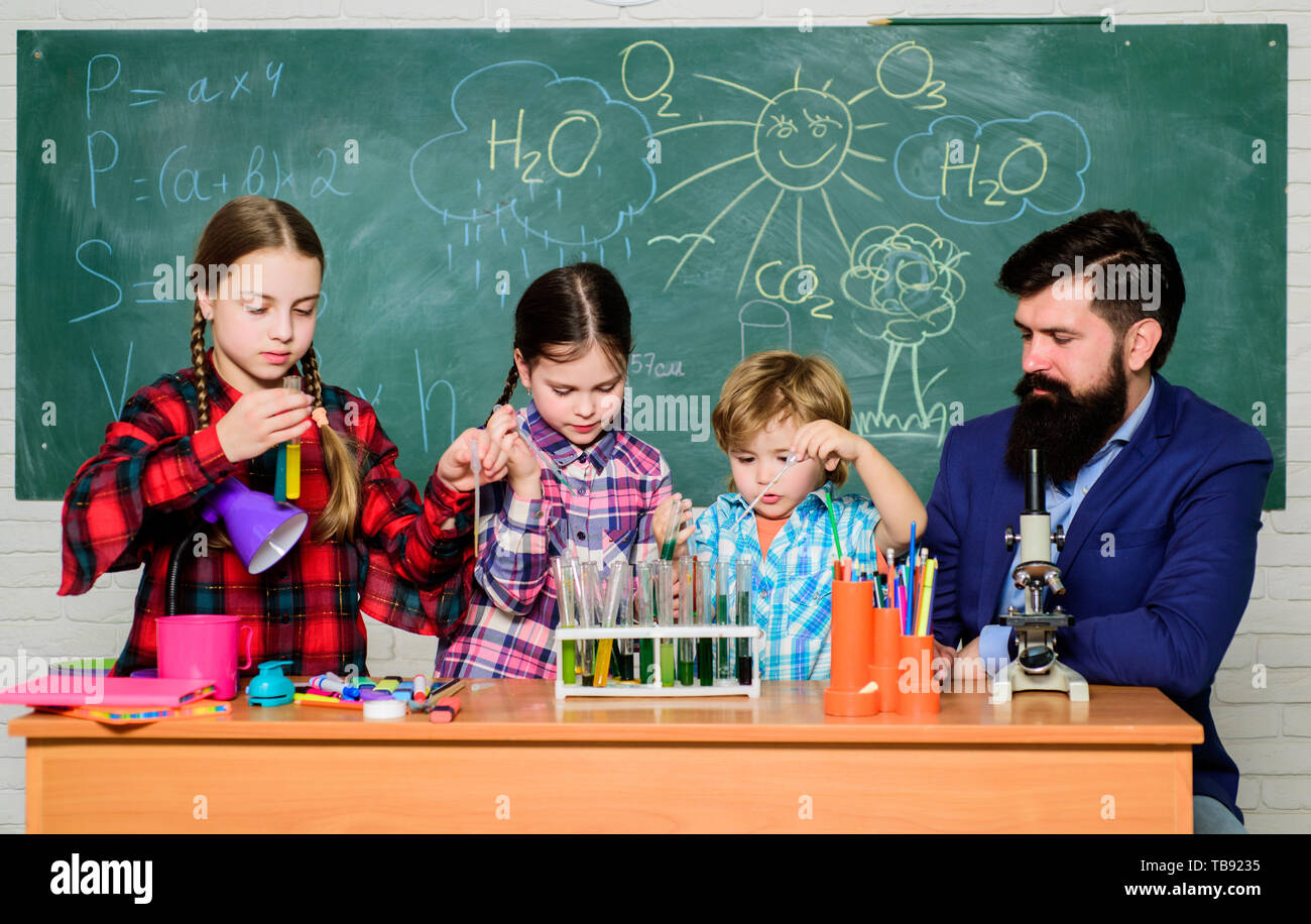 kids in lab coat learning chemistry in school laboratory. chemistry lab. happy children teacher. back to school. making experiment in lab or chemical cabinet. Research and development. Stock Photo