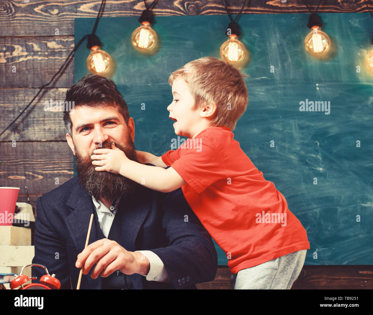 Childhood concept. Father painting while son is distracting him. Little kid holding his hand over daddy s mouth. Stock Photo