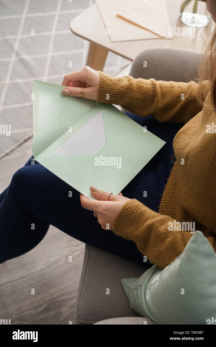 Young woman with received letter at home - Stock Image