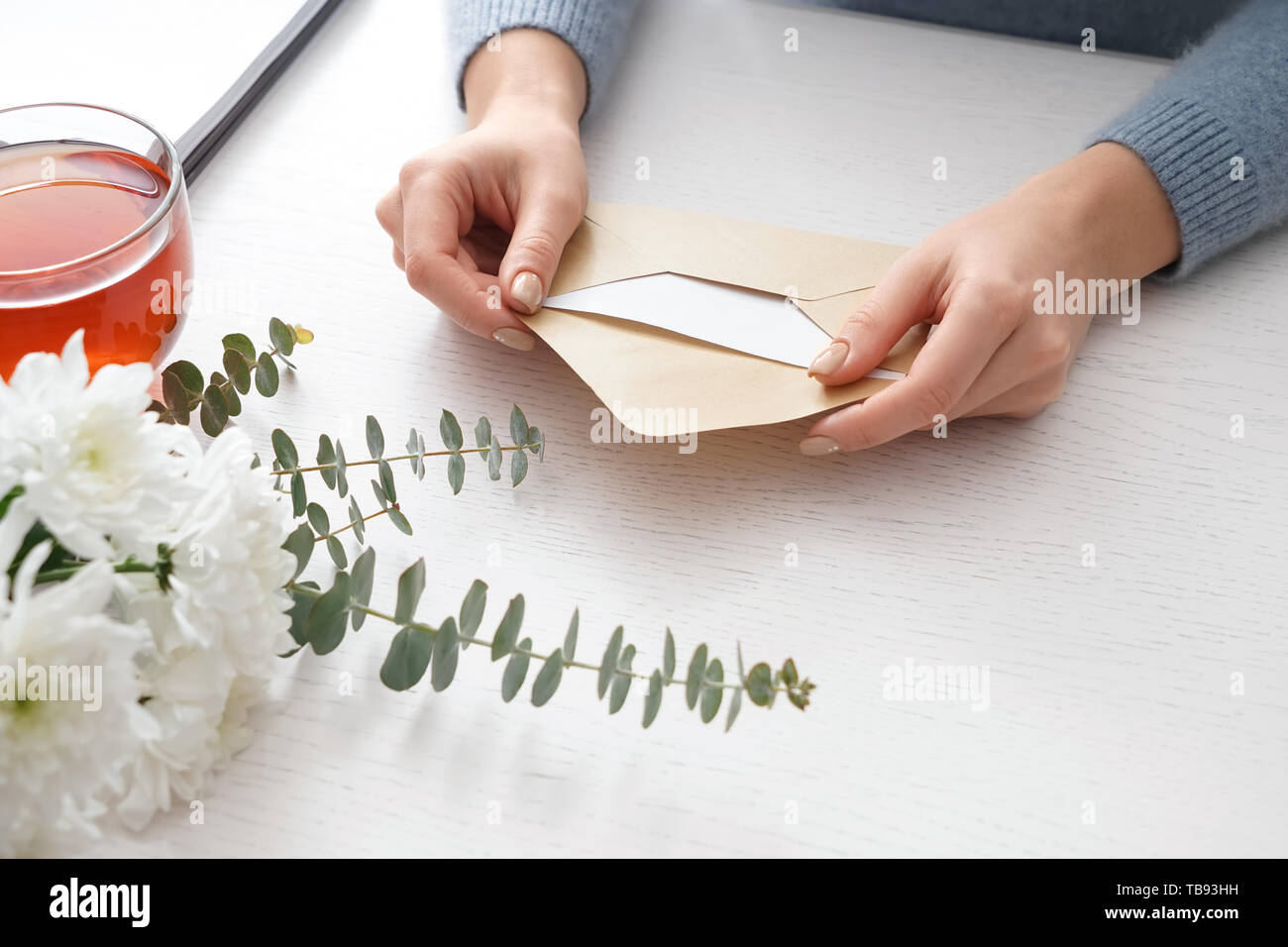 Young woman with received letter at table - Stock Image