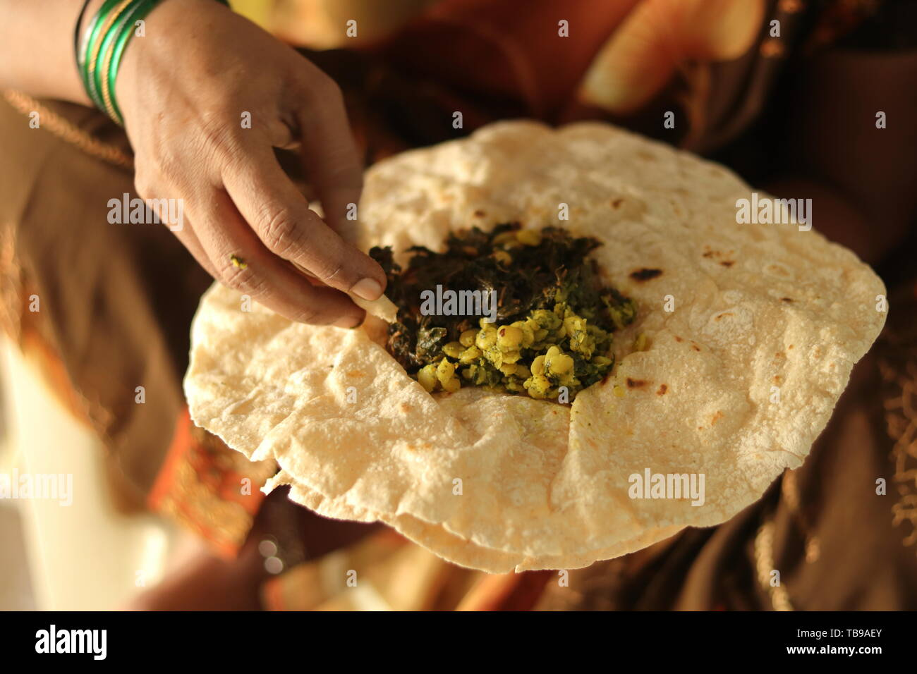 Closeup of woman eating South Indian north Karnataka peoples daily healhy breakfast Jowar roti or rotti or bhakri with dal curry in hand without using - Stock Image