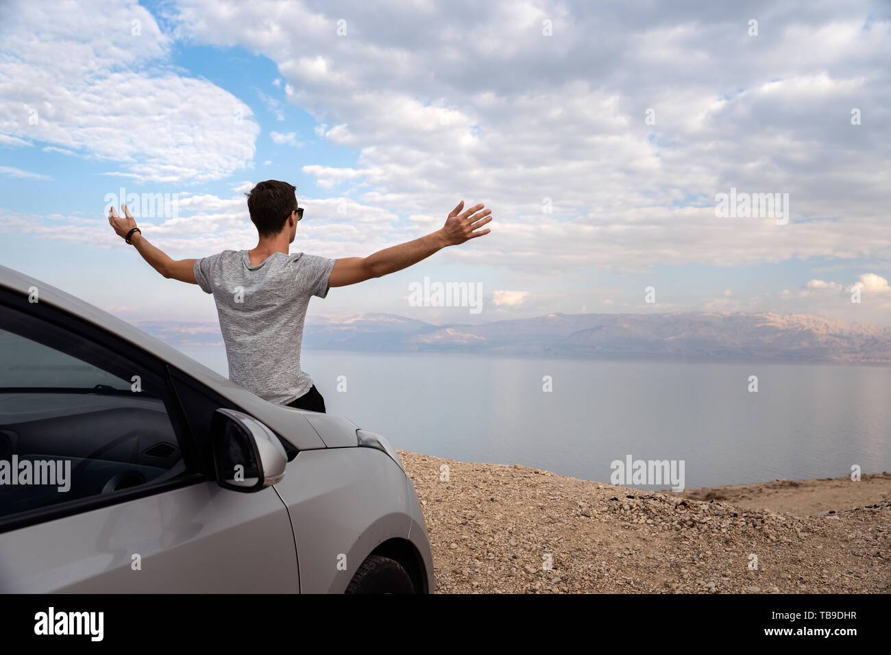 Man seated on the engine hood of a rented car. Dead sea as background - Stock Image