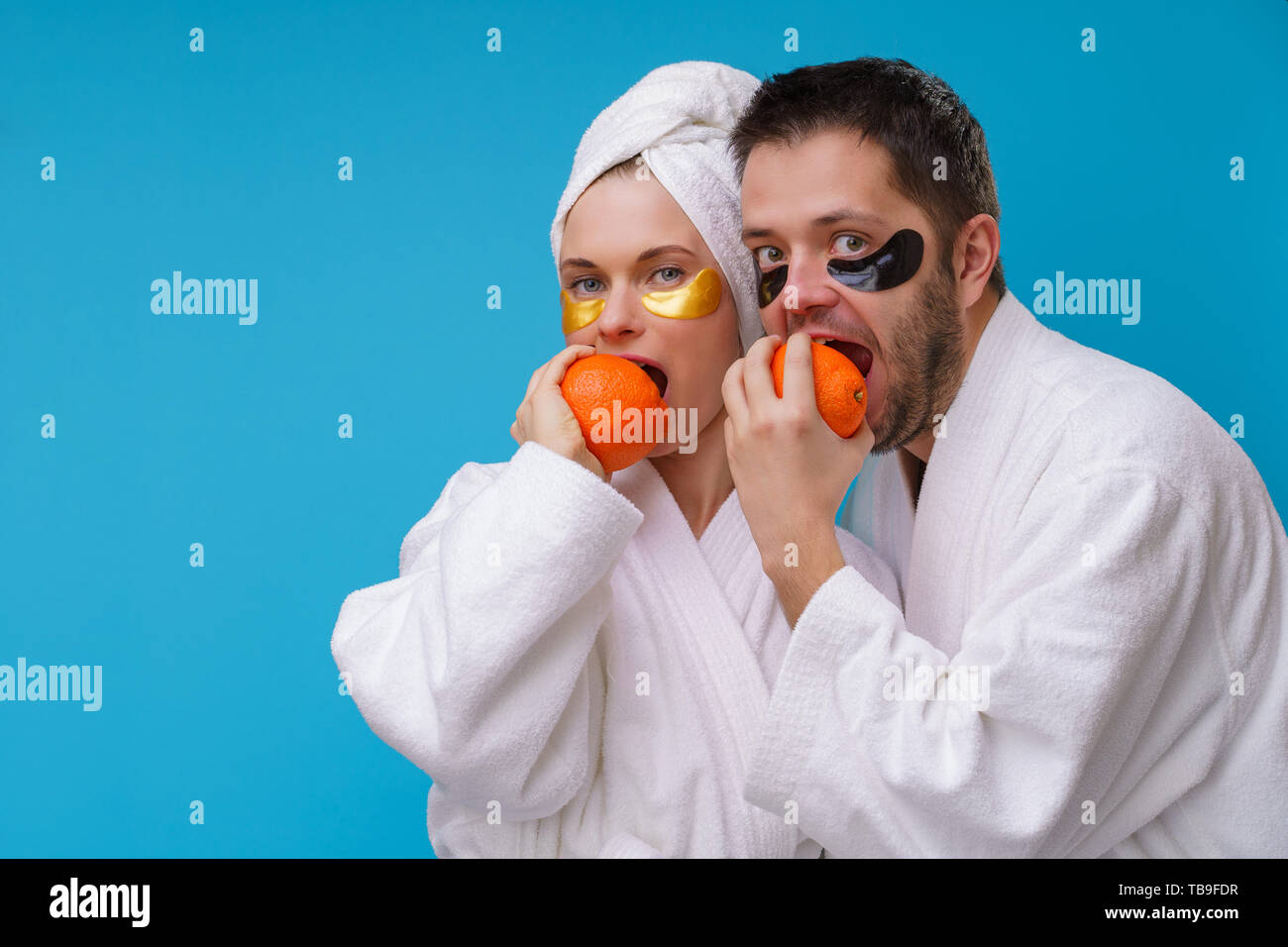 Photo of man and woman with gel pads under eyes and in white robe biting oranges - Stock Image
