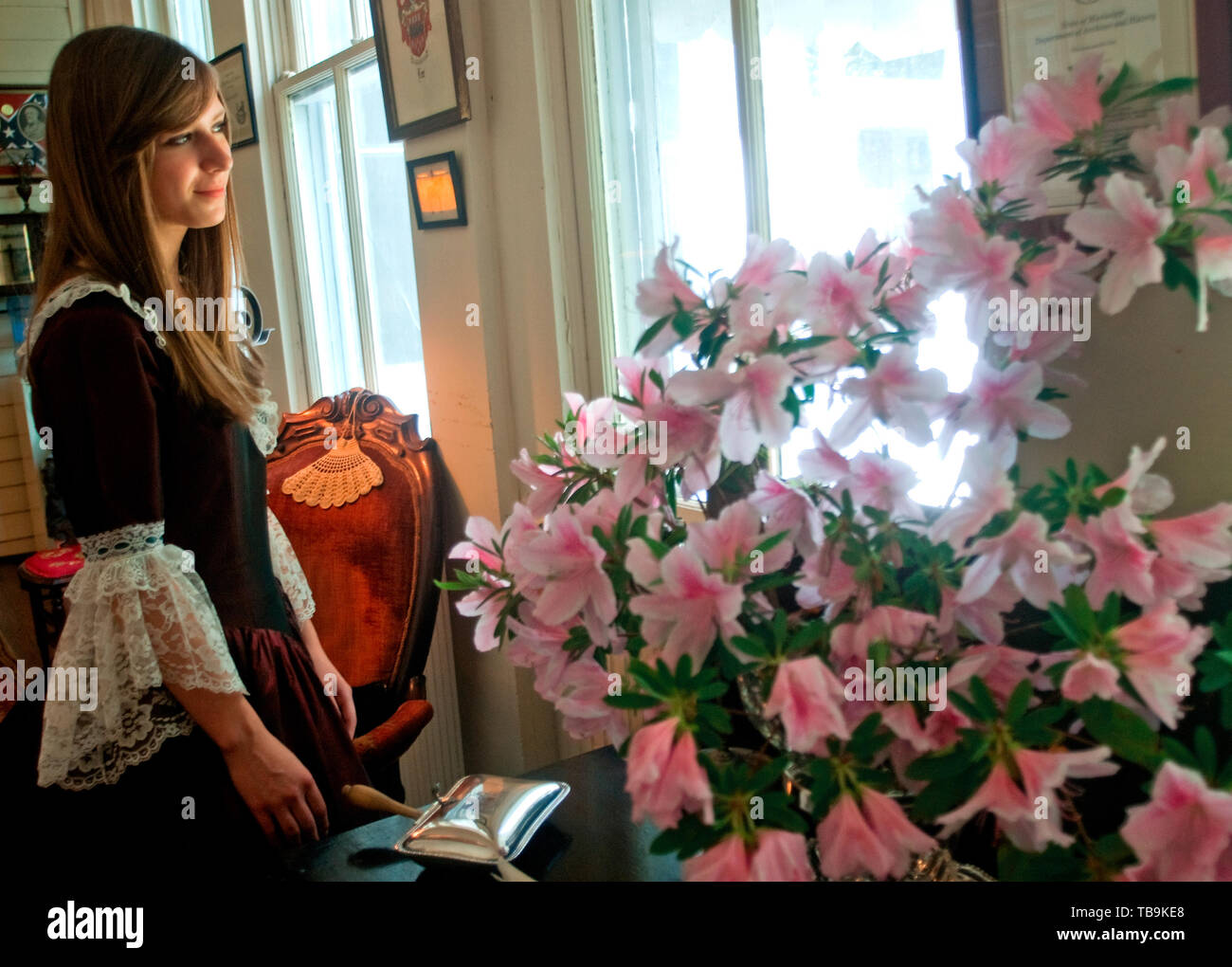 A tour guide, dressed in period costume, gazes out the window at the garden at the Amzi Love Home in Columbus, Mississippi, April 17, 2010. - Stock Image