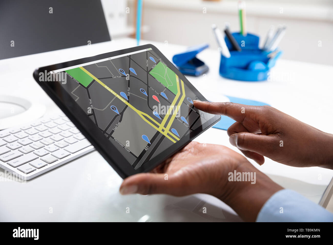 Close-up Of A Woman's Hand Using GPS Navigation Map On Digital Tablet Over The Desk - Stock Image