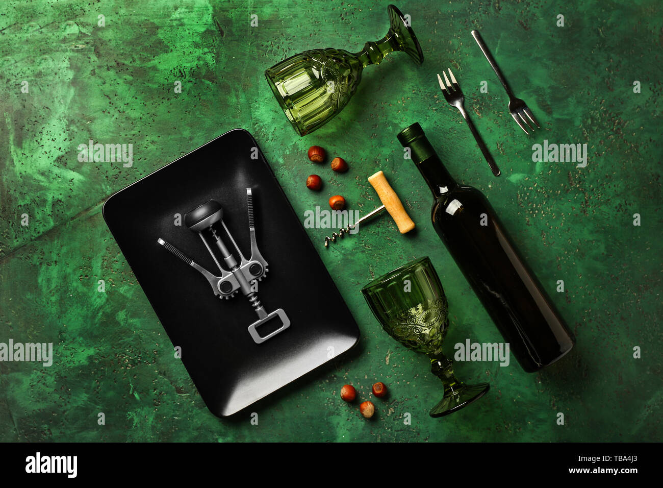 Glasses, bottle of wine, plate and corkscrews on color background - Stock Image