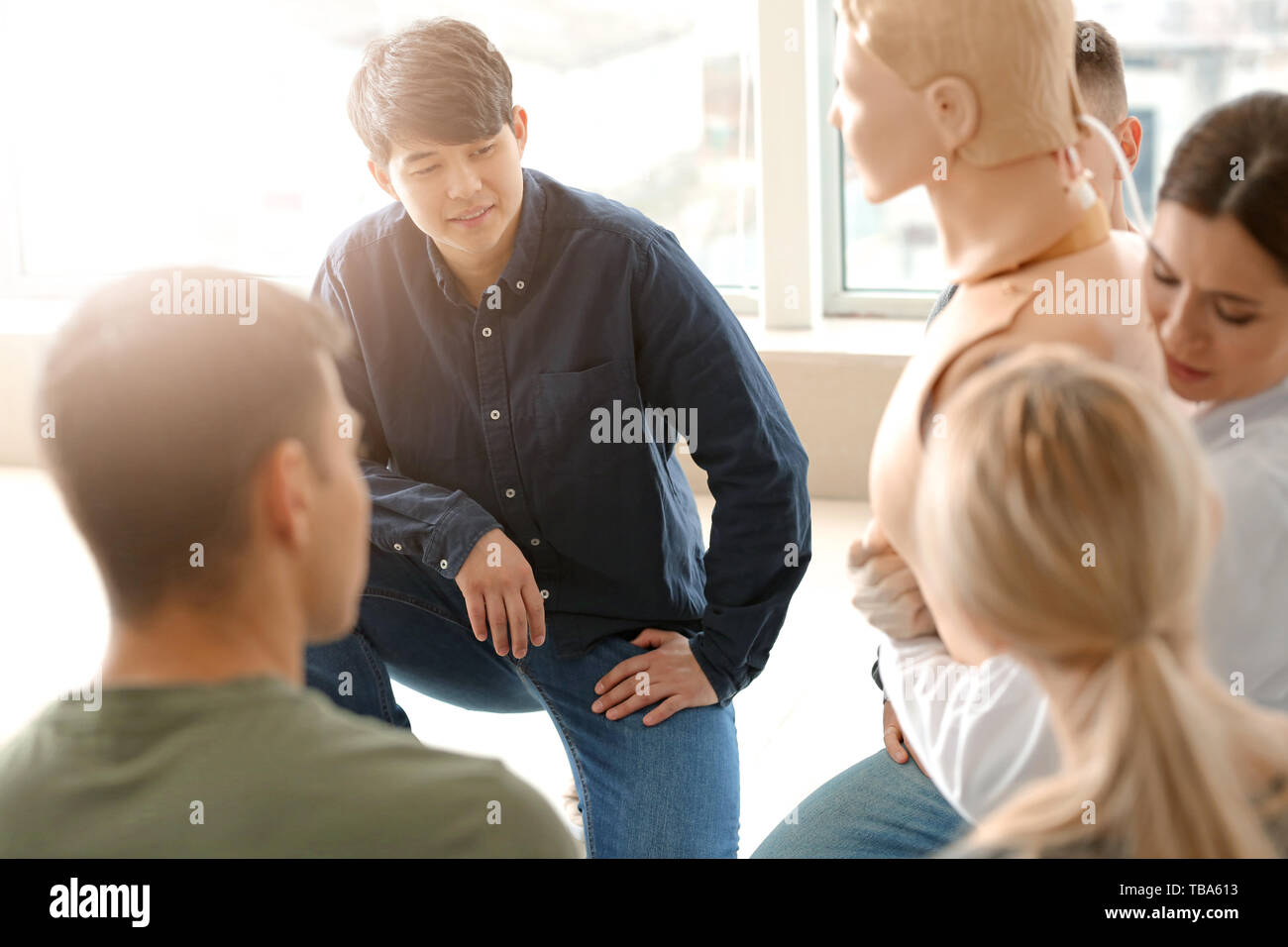 Instructor demonstrating what to do in case of choking at first aid training course - Stock Image
