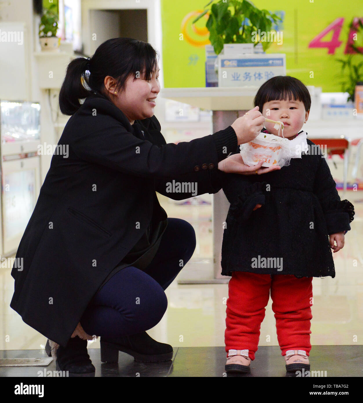 A Chinese mother feeding her little girl with noodles. - Stock Image