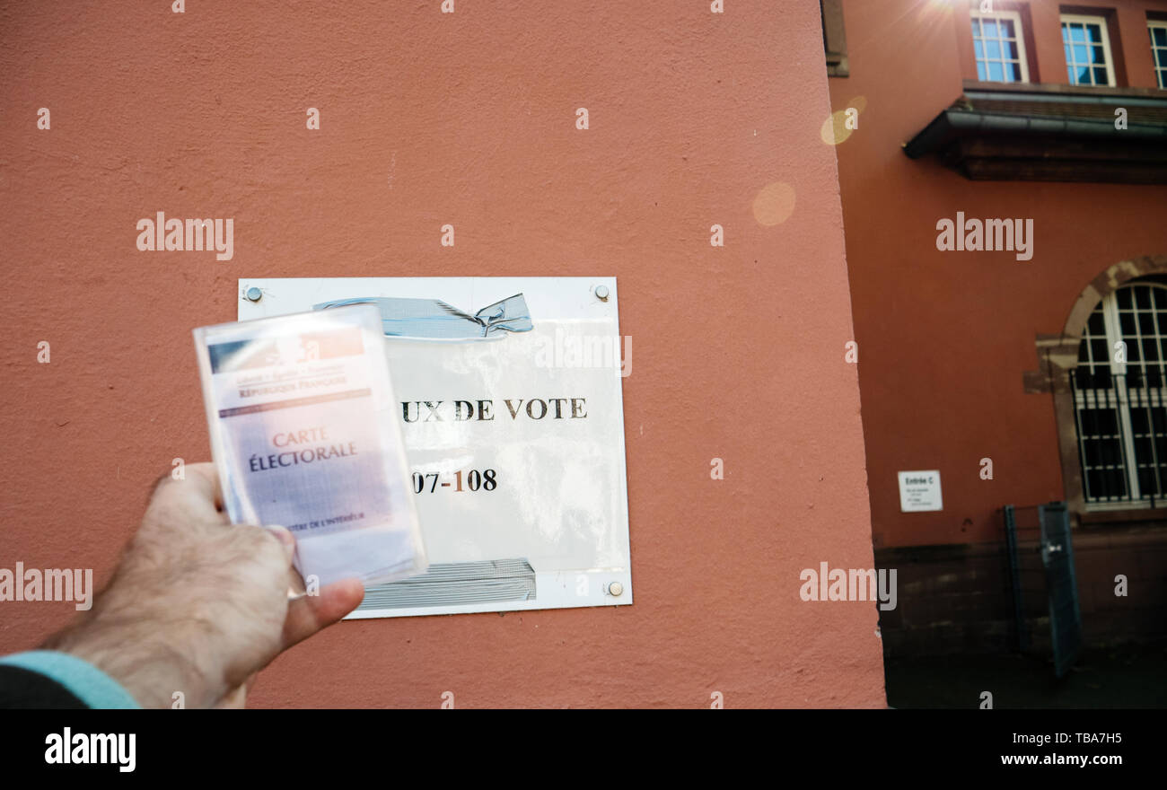 Strasbourg, France - May 26, 2019: Man hand holding Voter's car French Carte Electorale with entrance to polling station bureaux de vote in France on the 2019 European Parliament election day - Stock Image