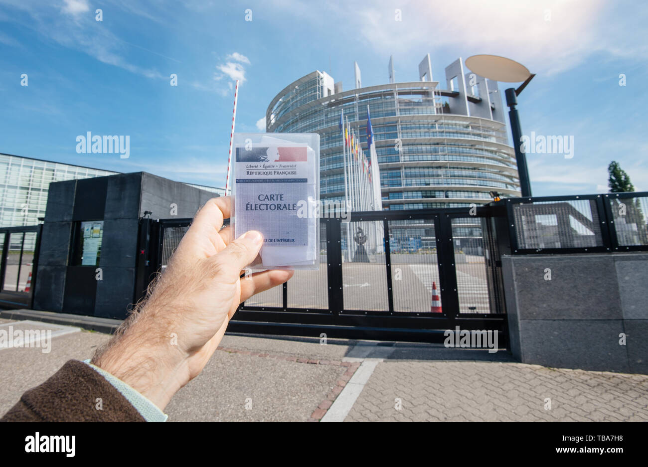 Strasbourg, France - May 26, 2019: man hand holding Voter's car French Carte Electorale at the entrance of European Parliament headquarter building with all flags on the 2019 European Parliament election day - Stock Image
