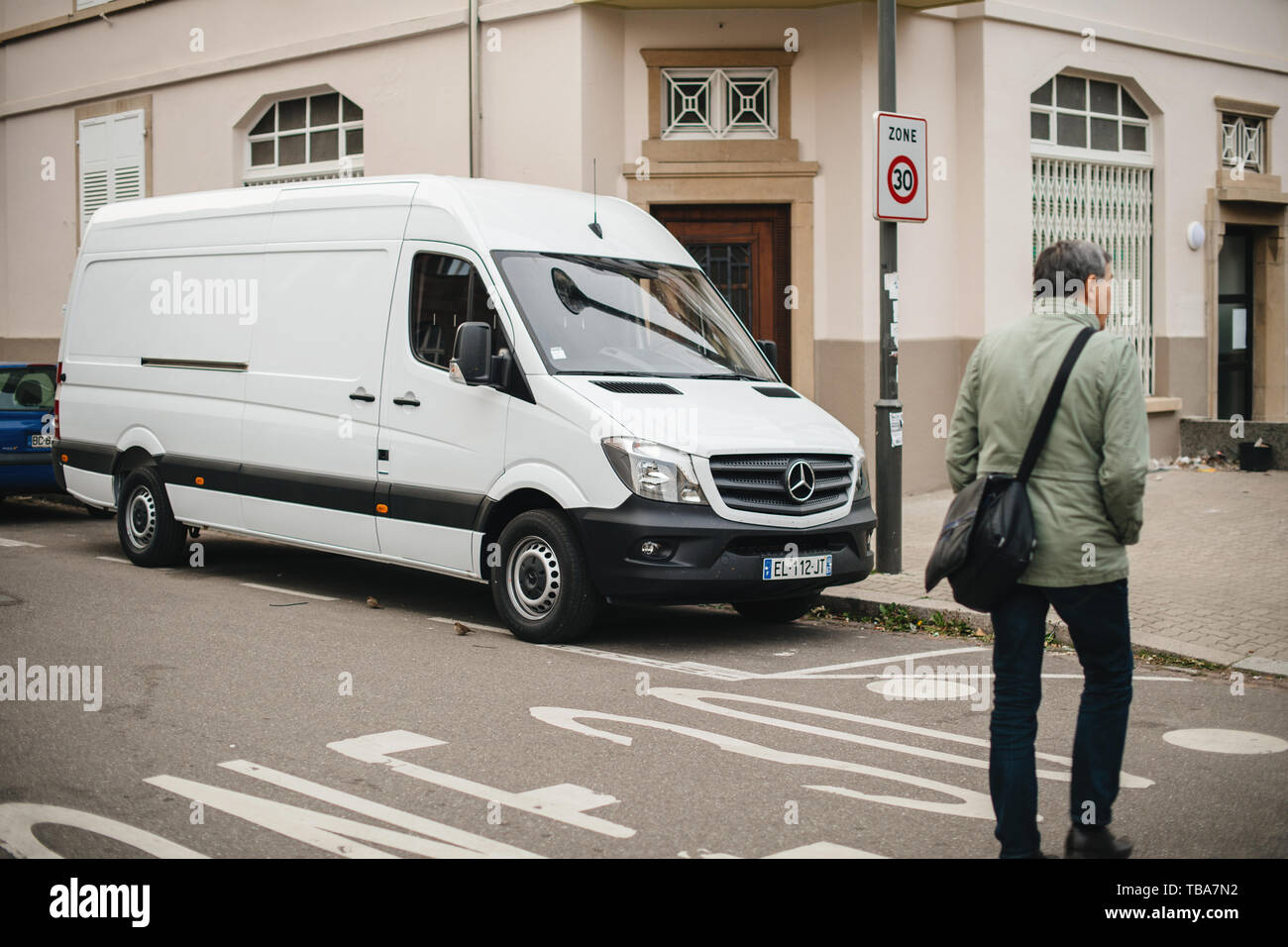 Strasbourg, France - Apr 5, 2017: Adult man crossing street in front of white Mercedes-Benz Sprinter van parked on French street  - delivery van - Stock Image