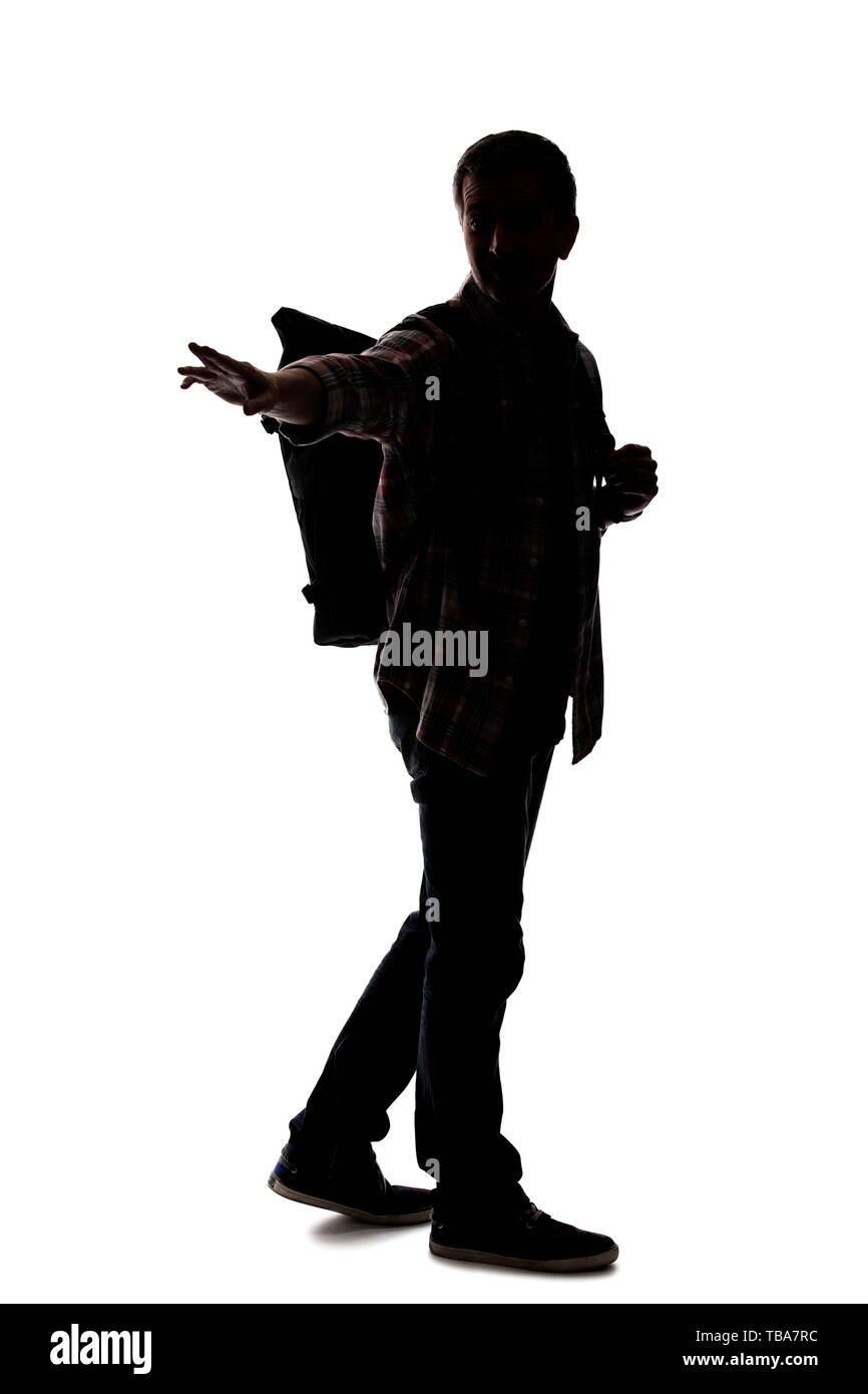 Silhouette of a male tour guide hiking and carrying a backpack on a white background.  He is pointing at something.  Depicts adventure and exploration - Stock Image