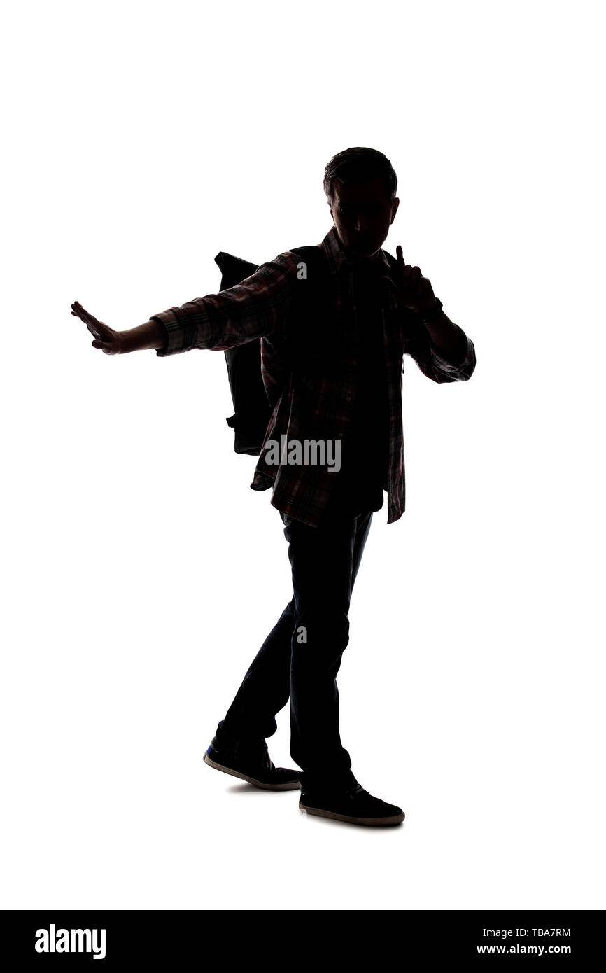 Silhouette of a male tour guide hiking and carrying a backpack on a white background.  He is carefully gesturing stop.  Depicts adventure and explorat - Stock Image
