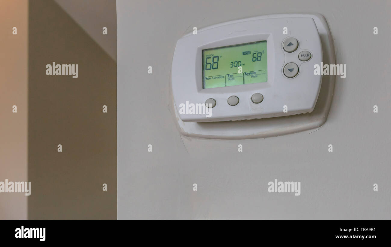 frame Panorama frame Wall mounted air conditioner unlit control and light switches inside a house - Stock Image