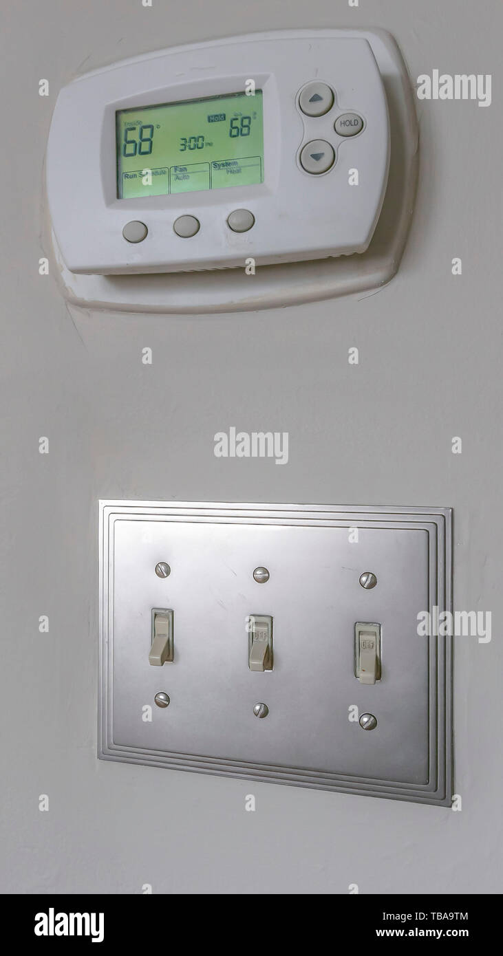 frame Vertical Wall mounted air conditioner unlit control and light switches inside a house - Stock Image