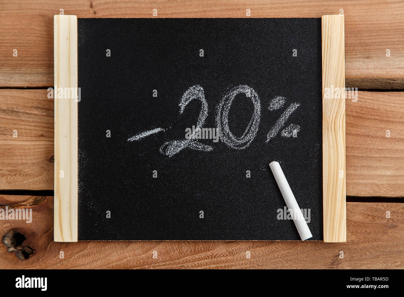 chalk Board with the inscription -20 percent on a wooden background. the view from the top Stock Photo
