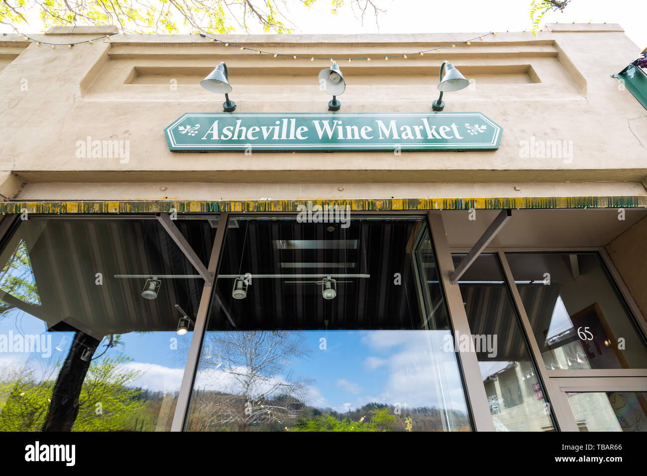 Asheville, USA - April 19, 2018: Downtown old town street in hipster North Carolina NC famous town with sign on building for Wine Market - Stock Image