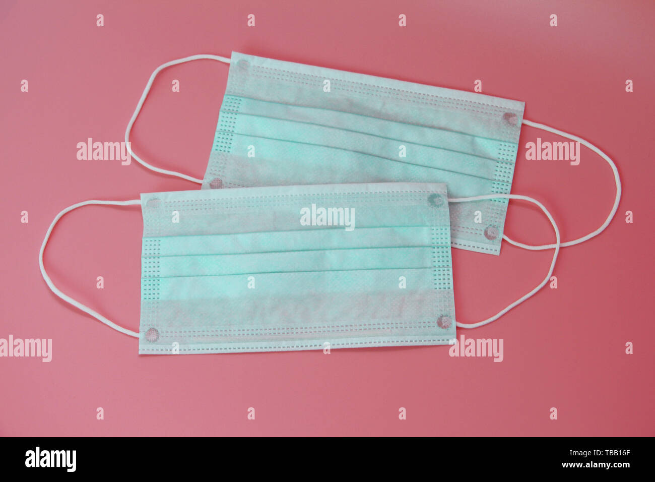 Two medical masks on a pink background. Disposable medical masks. There is not anyone. - Stock Image
