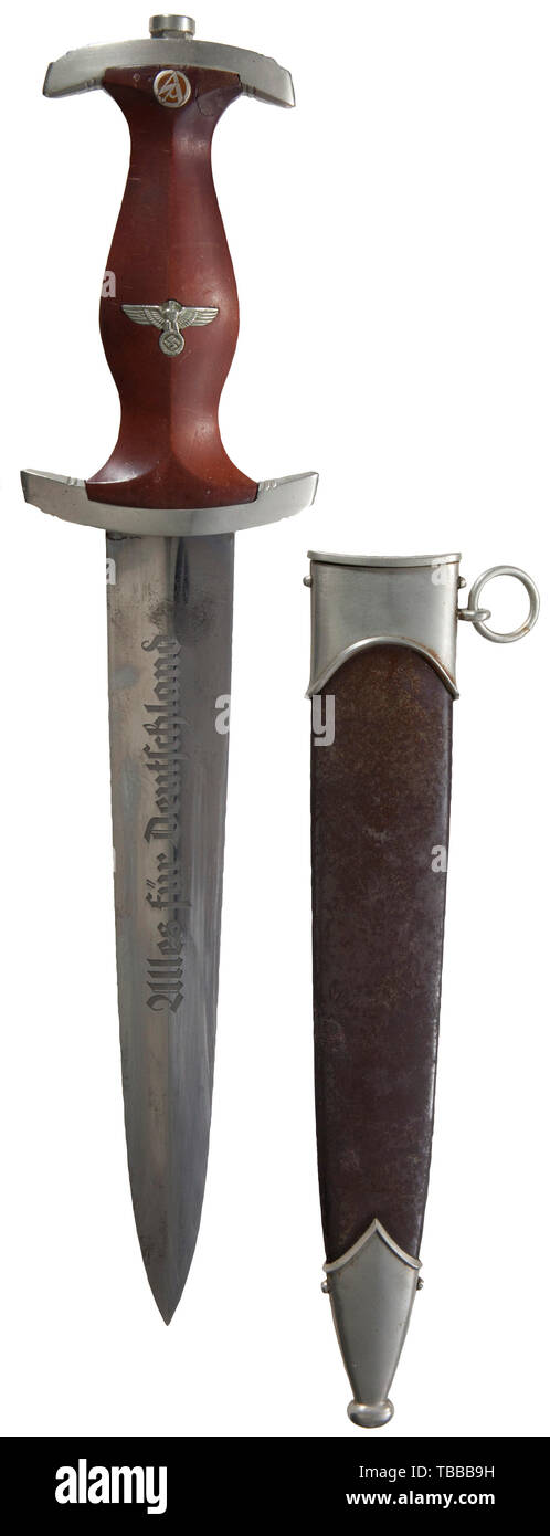 """THE JOHN PEPERA COLLECTION, A M 1933 SA Service Dagger, Maker Herm. Konejung A. G, Solingen. Polished blade (mild spotting) with etched motto and manufacturer's logo. Nickel silver hilt fittings, lower reverse crossguard stamped """"He"""" for SA Group Hessen. Brown wooden grip (repaired upper right corner) with inset nickel silver eagle and enamelled SA emblem. Burnished (thinning, minor corrosion) steel scabbard with traces of lacquer and nickel silver fittings. Length 37.5 cm., Editorial-Use-Only Stock Photo"""
