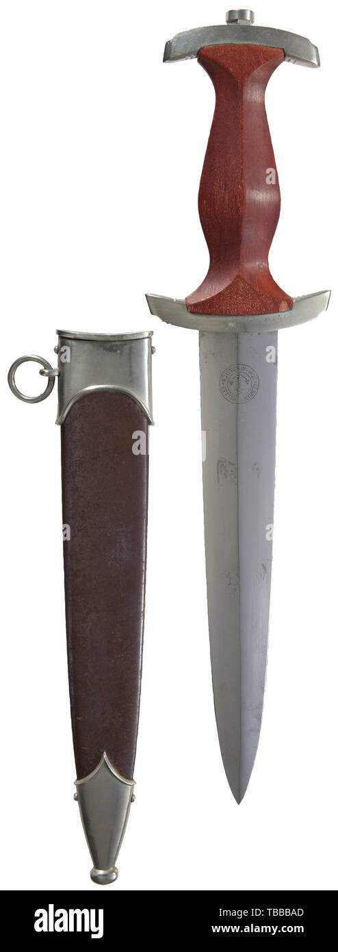 """THE JOHN PEPERA COLLECTION, A M 1933 SA Service Dagger, Maker Gebrüder Heller, Schmalkalden. Polished blade with etched motto and manufacturer's logo. Nickel silver hilt fittings, lower reverse crossguard stamped """"Mi"""" for SA Group Mitte. Brown wooden grip (small chip lower reverse right corner) with inset nickel silver eagle and enamelled SA emblem. Burnished steel scabbard with traces of lacquer (thinning/spotting) and nickel silver fittings (minor dent lower fitting)., Editorial-Use-Only Stock Photo"""