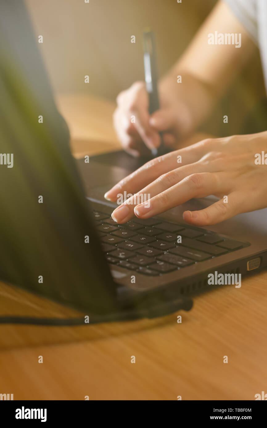 Illustrator using a graphics tablet. Woman's retoucher's hands using laptop and drawing tablet - Stock Image