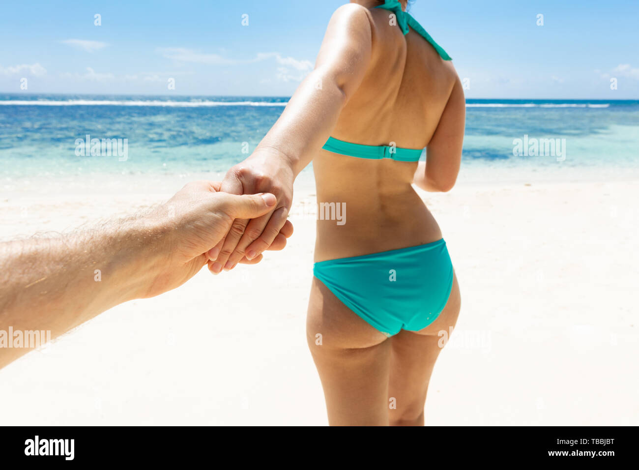 Close-up Of Woman In Bikini Holding The Hand Of Her Boyfriend On Beach - Stock Image