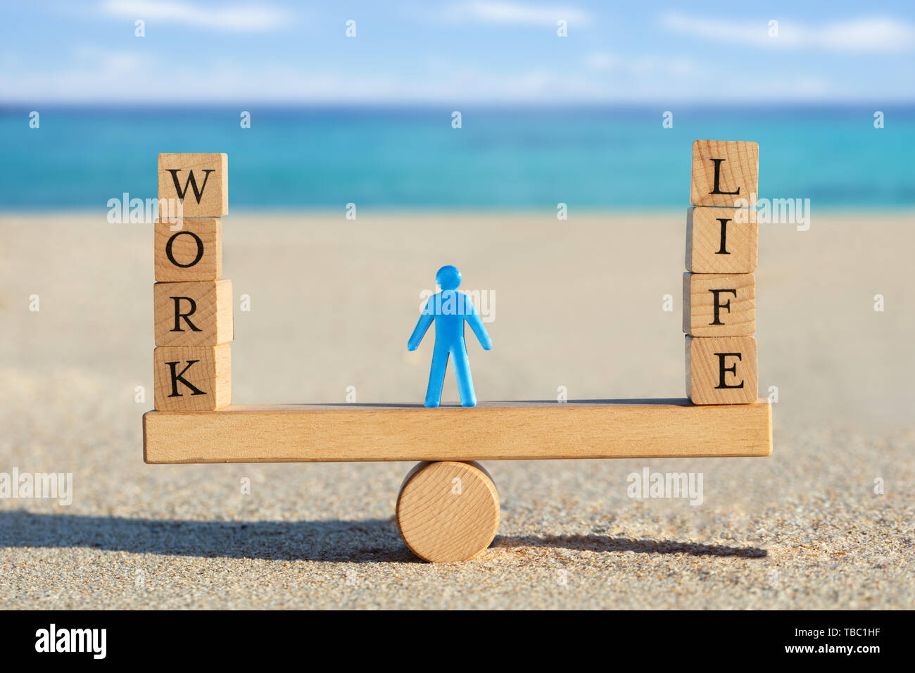 Blue Human Figure Standing Between The Work And Life Blocks Balancing On Seesaw At Beach - Stock Image