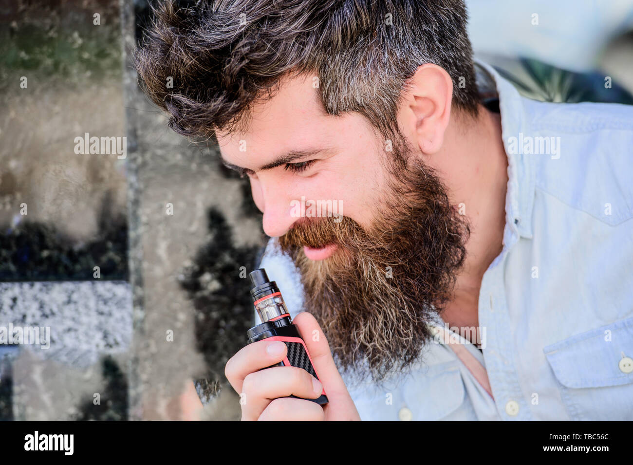Mature hipster with beard. Bearded brutal male smoking electronic cigarette. man smoking e-cigarette. hipster man hold vaping device. Health safety and addiction. inhaling vapor. Man smoking. - Stock Image