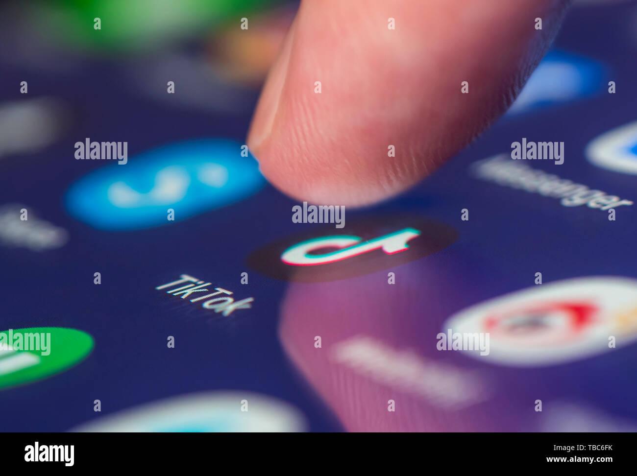 Finger pressing TikTok app icon (AKA Douyin) on a touchscreen on a tablet or mobile phone device. Loading Tik Tok application. TikTok shortcut. - Stock Image