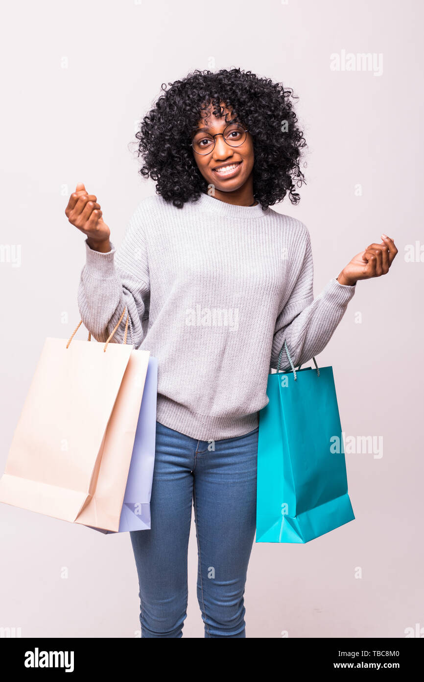 Excited shopping woman holding bags and smiling - isolated over white Stock Photo