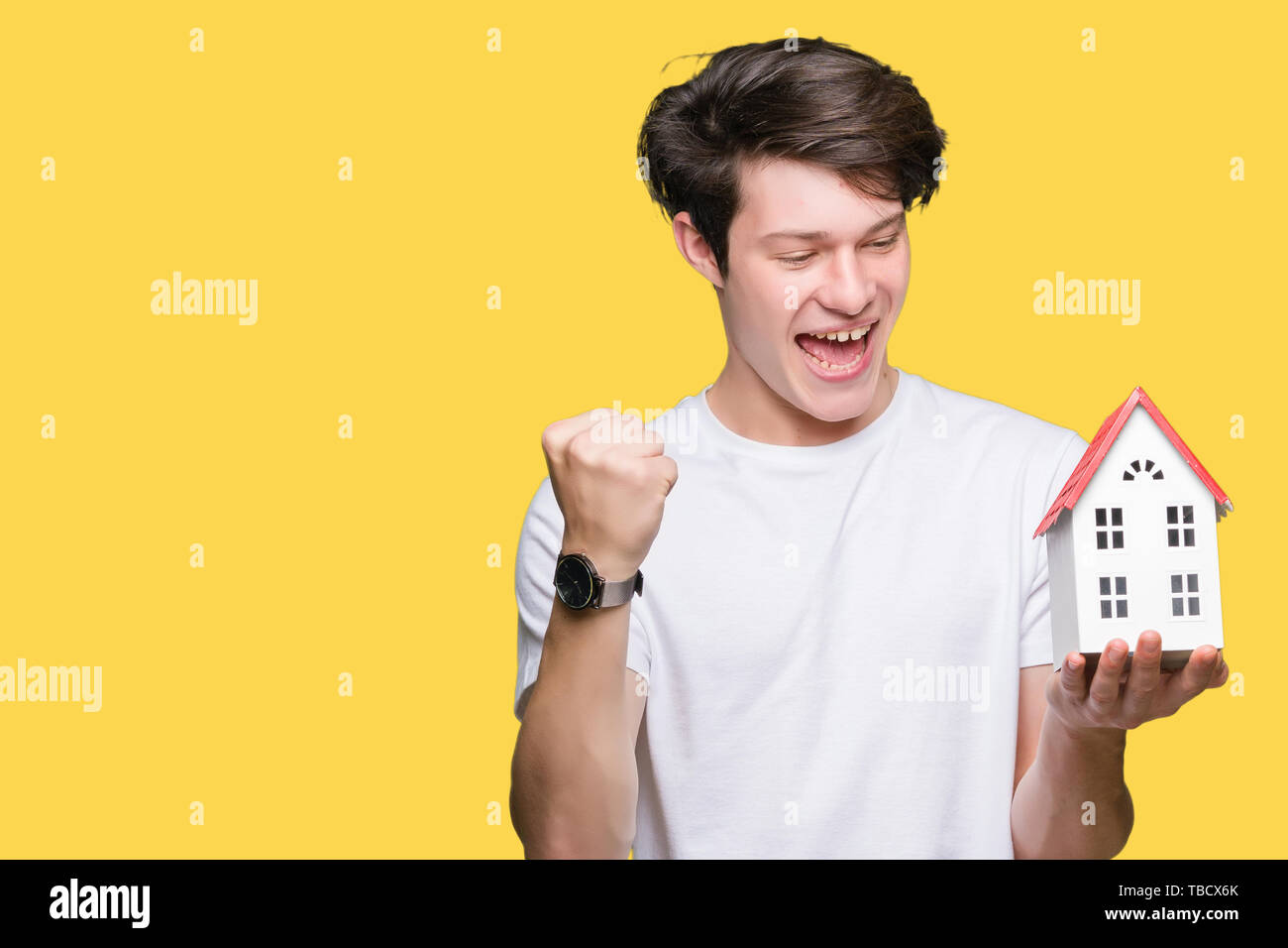 Young man holding house over isolated background screaming proud and celebrating victory and success very excited, cheering emotion - Stock Image