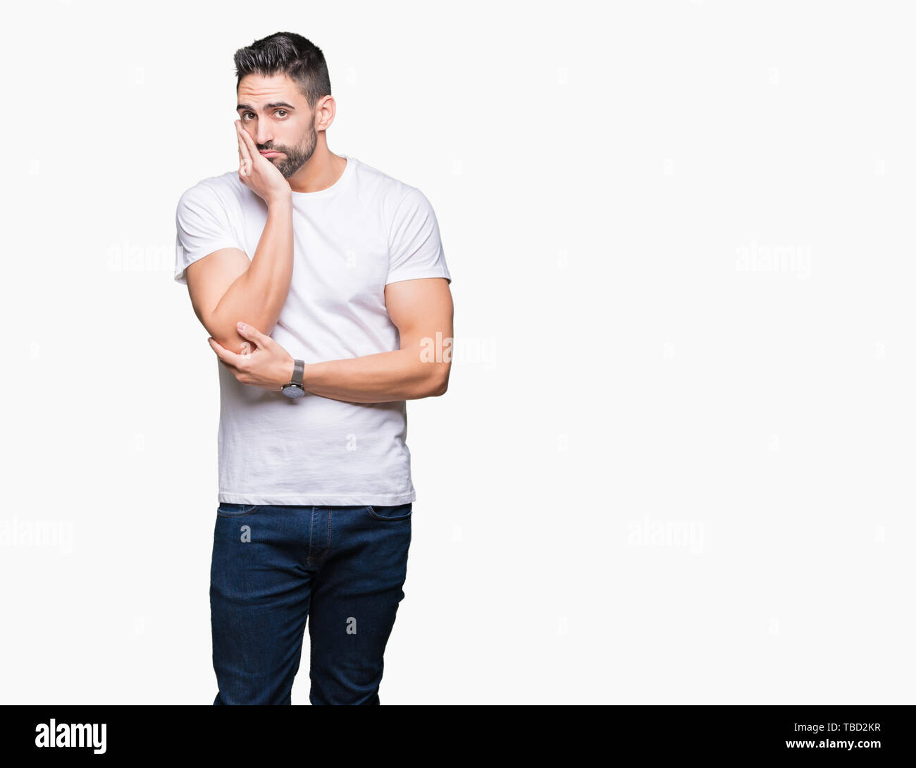 Young man wearing casual white t-shirt over isolated background thinking looking tired and bored with depression problems with crossed arms. Stock Photo