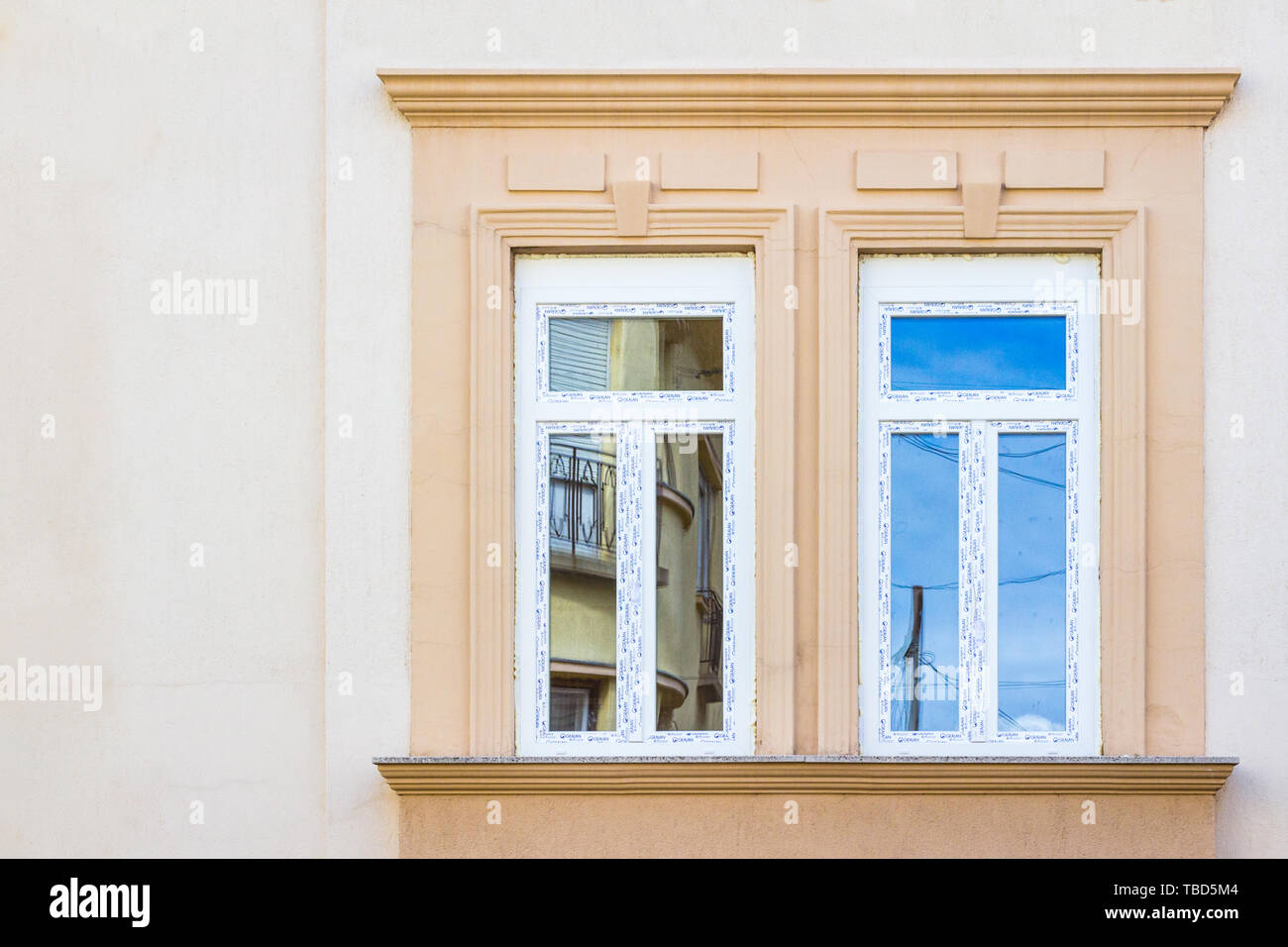 Two new replaced plastic windows on old renovated house - Stock Image